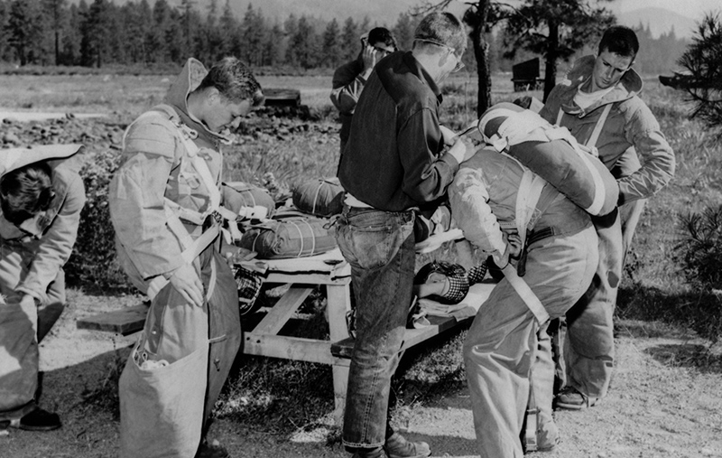 Men examining equipment for parachuting and firefighting
